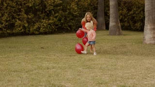 Mother and daughter playing with balloons in park