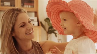 Mother and daughter playing with pink hat