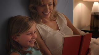 Mother and daughter reading in bed.