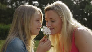 Mother and daughter smelling flower.