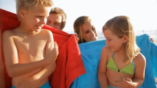 mother and father cuddling children on towels on beach