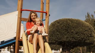 Mother and little girl on slide in playground