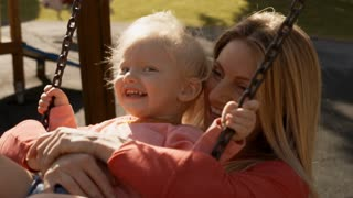 Mother and little girl on swing in playground