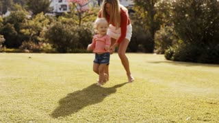 Mother chasing daughter in park