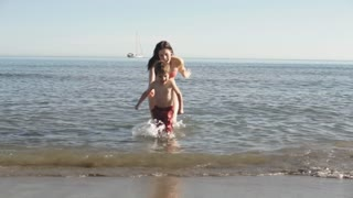 Mother chasing son out of sea.