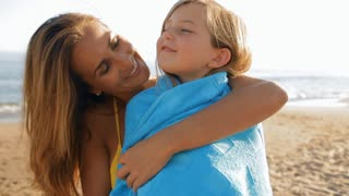mother cuddling daughter on beach in blue towel