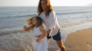 mother dancing with daughter on beach