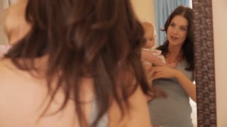 Mother holding baby girl up in mirror.