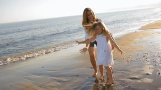 mother spinning daughter around on beach