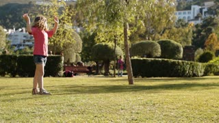One child doing cartwheels in park.