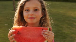 One child eating water melon in park.