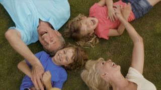 Overhead shot of grandparents and grandchildren lying on grass in garden.