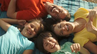 Overhead view of family with lying on rug in countryside.