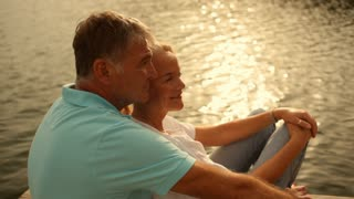 Pan shot of a mature couple sitting by lakeside in sunset
