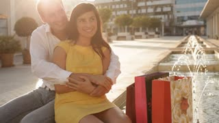 Pan shot of couple sitting by fountain with shopping bags