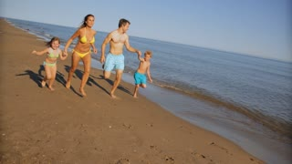 pan shot of family running on beach