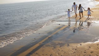 pan shot of family running towards camera on beach
