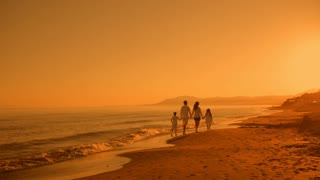 pan shot of family walking away from camera on beach in sunset