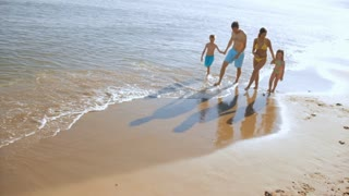 pan shot of family walking on beach
