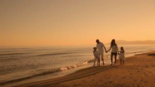 pan shot of family walking towards camera on beach in sunset