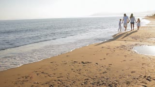pan shot of family walking towards camera on beach
