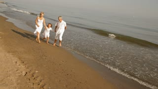 pan shot of grandparents and granddaughter running on beach