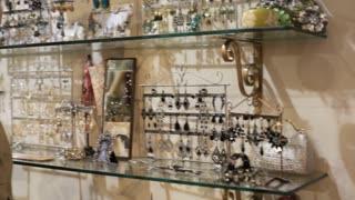 Pan shot of mature couple in shop looking at jewellery