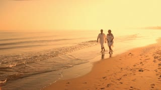 pan shot of senior couple running on beach in sunset