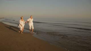 pan shot of senior couple running on beach