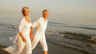 pan shot of senior couple running on beach