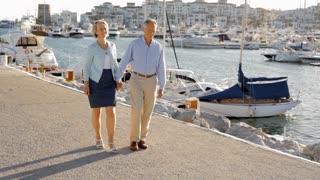 pan shot of senior couple walking by marina in sunset