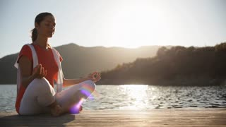 Pan shot of woman sitting by lakeside doing yoga