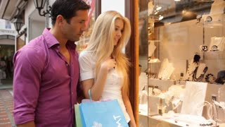 Pan shot of young couple in town looking in shop window