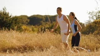pan shot of young couple running in the countryside