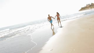 pan shot of young couple running on beach