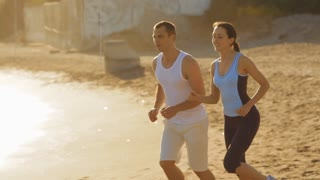 pan shot of young couple running on the beach
