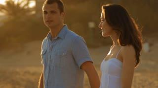 pan shot of young couple walking on beach