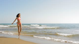 pan shot of young woman running on beach