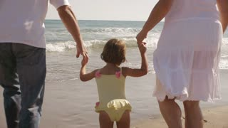 Parents and daughter running in the sea.