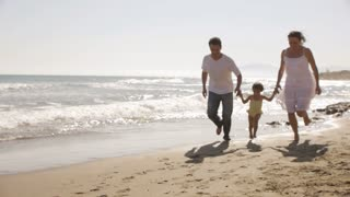 Parents and daughter running on beach.