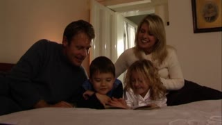 Parents putting children to bed, reading bedtime story
