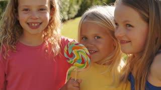 Portrait of three children licking lollypop in park.