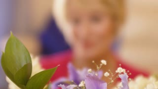 Rack focus shot of woman with flower arrangement.