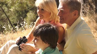 Senior couple and grandchild sitting in countryside enjoying views with binoculars.