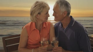 senior couple at beach cafe in sunset toasting camera