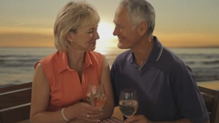 senior couple at beach cafe in sunset toasting each other