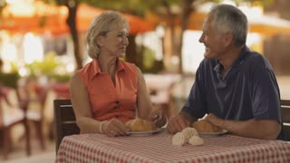 senior couple at cafe in town waiter bringing coffee