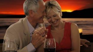 senior couple at dinner in sunset