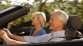 senior couple driving convertible car