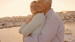 senior couple hugging by marina in sunset